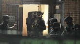 """Armed police officers work at a block of flats off Basingstoke Road in Reading after an incident at Forbury Gardens park in the town centre of Reading, England, Saturday, June 20, 2020. Several people were injured in a stabbing attack in the park on Saturday, and British media said police were treating it as """"terrorism-related."""" (Steve Parsons/PA via AP)"""