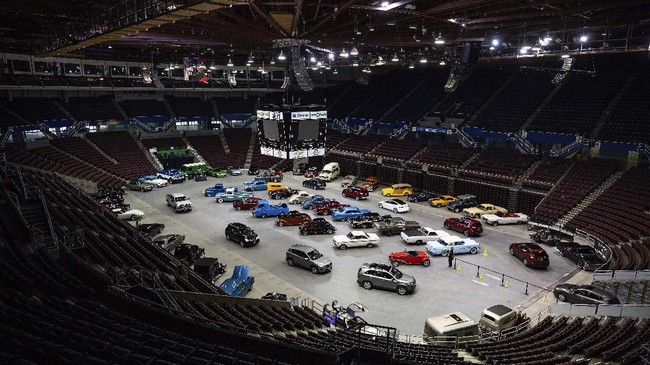 People attend a drive-thru classic and custom car show on the arena floor at Pacific Coliseum, in Vancouver, British Columbia, Sunday, June 21, 2020. The car show was hosted by the Pacific National Exhibition as part of a drive-thru barbecue event in support of food vendors unable to sell at the fair this year due to the cancellation of the annual event because of the coronavirus. (Darryl Dyck/The Canadian Press via AP)
