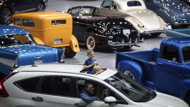 Children stand through a sunroof while attending a drive-thru classic and custom car show on the arena floor at Pacific Coliseum, in Vancouver, British Columbia, Sunday, June 21, 2020. The car show was hosted by the Pacific National Exhibition as part of a drive-thru barbecue event in support of food vendors unable to sell at the fair this year due to the cancellation of the annual event because of the coronavirus. (Darryl Dyck/The Canadian Press via AP)