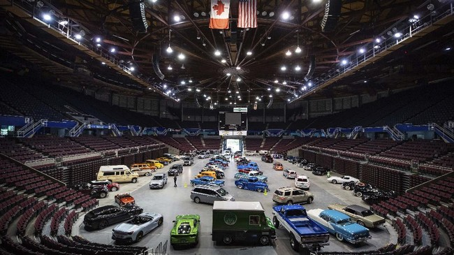 People attend a drive-thru classic and custom car show on the arena floor at Pacific Coliseum in Vancouver, British Columbia, Sunday, June 21, 2020. The car show was hosted by the Pacific National Exhibition as part of a drive-thru barbecue event in support of food venders unable to sell at the fair this year due to the cancellation of the annual event because of COVID-19. (Darryl Dyck/The Canadian Press via AP)