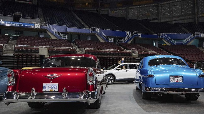 Children stand through a sunroof while attending a drive-thru classic and custom car show on the arena floor at Pacific Coliseum in Vancouver, British Columbia, Sunday, June 21, 2020. The car show was hosted by the Pacific National Exhibition as part of a drive-thru barbecue event in support of food venders unable to sell at the fair this year due to the cancellation of the annual event because of COVID-19. (Darryl Dyck/The Canadian Press via AP)