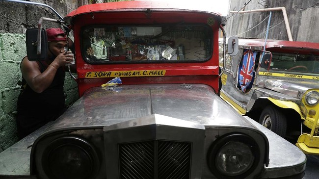 A jeepney driver drinks coffee beside his vehicle at the Tandang Sora terminal which have been home for them since a lockdown started three months ago, on Wednesday, June 17, 2020 in Quezon city, Philippines. About 35 jeepney drivers were forced to stay due to travel restrictions and have made jeepneys their home as the government banned public transport during the community quarantine to prevent the spread of the new coronavirus. Many of the jobless drivers have resorted to begging in the streets, displaying cardboard signs scrawled with pleas for money and food on their multi-colored jeepneys. (AP Photo/Aaron Favila)