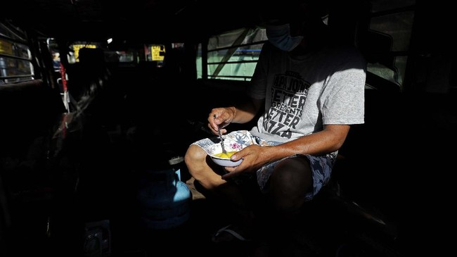 Driver Michael Navarra prepares egg to be cooked for their afternoon snack inside a jeepney at the Tandang Sora terminal which have been home for them since a lockdown started three months ago, on Wednesday, June 17, 2020 in Quezon city, Philippines. About 35 jeepney drivers were forced to stay due to travel restrictions and have made jeepneys their home as the government banned public transport during the community quarantine to prevent the spread of the new coronavirus. Many of the jobless drivers have resorted to begging in the streets, displaying cardboard signs scrawled with pleas for money and food on their multi-colored jeepneys. (AP Photo/Aaron Favila)