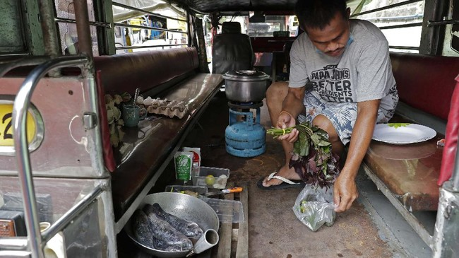 Driver Michael Navarra cooks fish and vegetables on their portable stove inside a jeepney at the Tandang Sora terminal which have been home for them since the lockdown started three months ago, on Wednesday, June 17, 2020 in Quezon city, Philippines. About 35 jeepney drivers were forced to stay due to travel restrictions and have made jeepneys their home as the government banned public transport during the community quarantine to prevent the spread of the new coronavirus. Many of the jobless drivers have resorted to begging in the streets, displaying cardboard signs scrawled with pleas for money and food on their multi-colored jeepneys. (AP Photo/Aaron Favila)