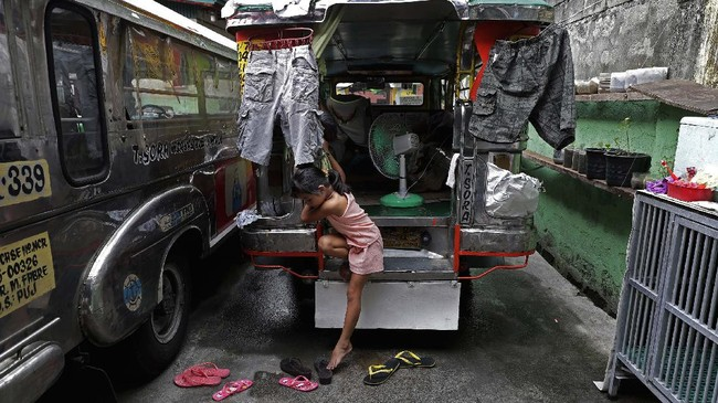 Seven-year-old Yuna Recio comes down from their passenger jeepney at the Tandang Sora terminal which have been home for her family during a lockdown, on Wednesday, June 17, 2020 in Quezon city, Philippines. About 35 jeepney drivers were forced to stay due to travel restrictions and have made jeepneys their home as the government banned public transport during the community quarantine to prevent the spread of the new coronavirus. Many of the jobless drivers have resorted to begging in the streets, displaying cardboard signs scrawled with pleas for money and food on their multi-colored jeepneys. (AP Photo/Aaron Favila)