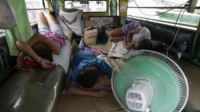 The Recio family sleeps inside their passenger jeepney at a terminal which have been home for them on Wednesday, June 17, 2020 in Quezon city, Philippines. About 35 jeepney drivers were forced to stay due to travel restrictions and have made jeepneys their home as the government banned public transport during the community quarantine to prevent the spread of the new coronavirus. Many of the jobless drivers have resorted to begging in the streets, displaying cardboard signs scrawled with pleas for money and food on their multi-colored jeepneys. (AP Photo/Aaron Favila)