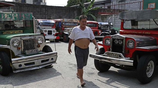 Driver Jude Recio walks past jeepneys parked at the Tandang Sora terminal which have been home for them since a lockdown started three months ago, on Wednesday, June 17, 2020 in Quezon city, Philippines. About 35 jeepney drivers were forced to stay due to travel restrictions and have made jeepneys their home as the government banned public transport during the community quarantine to prevent the spread of the new coronavirus. Many of the jobless drivers have resorted to begging in the streets, displaying cardboard signs scrawled with pleas for money and food on their multi-colored jeepneys. (AP Photo/Aaron Favila)