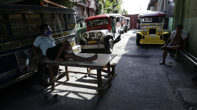 Driver Rey Escanilla, left, sits beside parked jeepneys at the Tandang Sora terminal which have been home for them since a lockdown started three months ago, on Wednesday, June 17, 2020 in Quezon city, Philippines. Espanilla was kicked out of their home after failing to pay their monthly rent during the pandemic. He has now relocated his family to another place but remains jobless. (AP Photo/Aaron Favila)