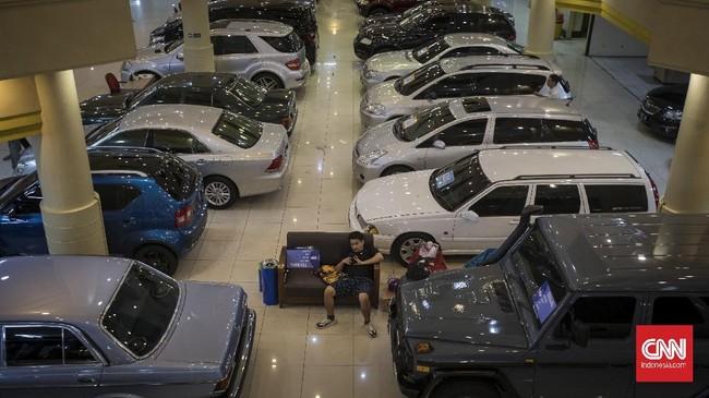 Seorang warga duduk di dekat mobil yang dijual di Bursa Mobil Bekas Blok M. Jakarta, Rabu, 24 Juni 2020. Angka permintaan mobil bekas yang merosot salah satu di antaranya disebabkan oleh perilaku konsumen yang cenderung menahan pengeluaran di tengah pandemi. Penurunan permintaan mobil bekas saat ini turun hingga 60 - 90 persen dari situasi normal, akibatnya harga mobil bekas terjun bebas atau turun drastis. CNN Indonesia/Adhi Wicaksono.