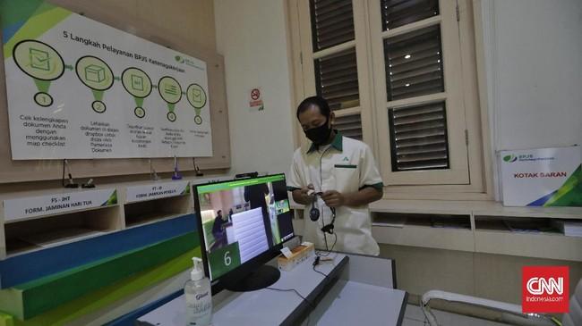 Pekerja mensterilkan bilik setelah peserta BP Jamsostek berkomunikasi dengan petugas pelayanan melalui layar monitor dan tanpa kontak langsung saat mengurus klaim di Kantor Cabang BP Jamsostek Salemba.(CNN Indonesia/ Adhi Wicaksono)