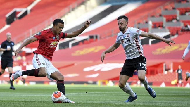 Manchester United's Mason Greenwood, left, controls the ball as Sheffield United's Jack Robinson defends during the English Premier League soccer match between Manchester United and Sheffield United at Old Trafford in Manchester, England, Wednesday, June 24, 2020. (Michael Regan/Pool via AP)