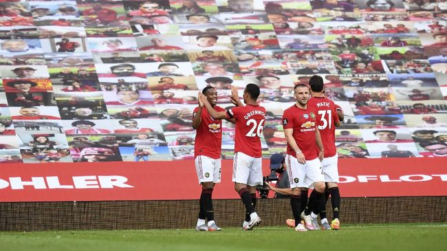 Manchester United's Anthony Martial, left, celebrates with his teammates, after scoring his side's third goal during the English Premier League soccer match between Manchester United and Sheffield United at Old Trafford in Manchester, England, Wednesday, June 24, 2020. (Michael Regan/Pool via AP)