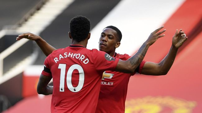 Manchester United's Anthony Martial, right, celebrates after scoring the opening goal of his team during the English Premier League soccer match between Manchester United and Sheffield United at Old Trafford in Manchester, England, Wednesday, June 24, 2020. (Michael Regan/Pool via AP)