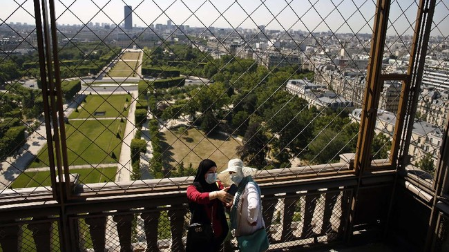Visitors take a selfie from the first floor of the Eiffel Tower, in Paris, Thursday, June 25, 2020. The Eiffel Tower reopens after the coronavirus pandemic led to the iconic Paris landmark's longest closure since World War II. (AP Photo/Thibault Camus)