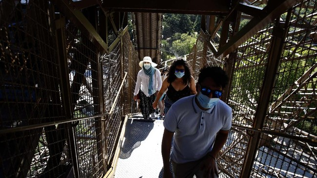 People climb stairs as they visit the Eiffel Tower, in Paris, Thursday, June 25, 2020. The Eiffel Tower reopens after the coronavirus pandemic led to the iconic Paris landmark's longest closure since World War II. (AP Photo/Thibault Camus)