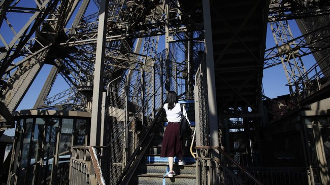 A visitor climbs the stairs of the Eiffel Tower, in Paris, Thursday, June 25, 2020. The Eiffel Tower reopens after the coronavirus pandemic led to the iconic Paris landmark's longest closure since World War II. (AP Photo/Thibault Camus)