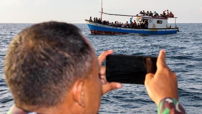 Anggota Marinir mengabadikan kapal yang ditumpangi pengungsi etnis Rohingya saat ditarik dari tengah laut menuju pesisir Bayu, Aceh Utara, Aceh, Rabu (24/6/2020). Sebanyak 94 orang pengungsi etnis Rohingya, terdiri dari 15 orang laki-laki, 49 orang perempuan dan 30 orang anak-anak ditemukan terdampar di tengah laut dengan kondisi kapal rusak, sebanyak 15 orang lainnya dilaporkan meninggal di laut selama mereka terdampar di perairan Indonesia hingga ke Aceh. ANTARA FOTO/Rahmad.