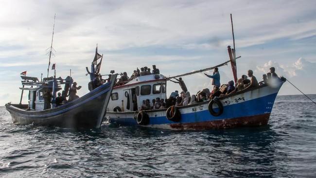 Kapal nelayan (kiri) mengikat kapal yang ditumpangi pengungsi etnis Rohingya untuk ditarik dari tengah laut menuju pesisir Bayu, Aceh Utara, Aceh, Rabu (24/6/2020). Sebanyak 94 orang pengungsi etnis Rohingya, terdiri dari 15 orang laki-laki, 49 orang perempuan dan 30 orang anak-anak ditemukan terdampar di tengah laut dengan kondisi kapal rusak, sementara sebanyak 15 orang lainnya dilaporkan meninggal di laut selama mereka terdampar di perairan Indonesia hingga ke Aceh. ANTARA FOTO/Rahmad/foc.