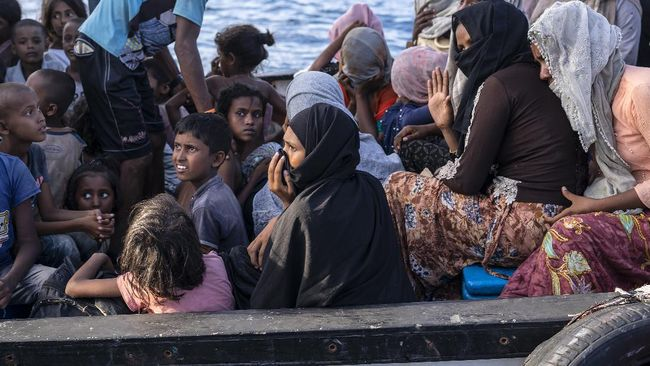 Ethnic Rohingya people sit on the deck of a boat off North Aceh, Indonesia, Wednesday, June 24, 2020. Indonesian fishermen discovered dozens of hungry, weak Rohingya Muslims on the wooden boat adrift off Indonesia's northernmost province of Aceh, an official said. (AP Photo/Zik Maulana)