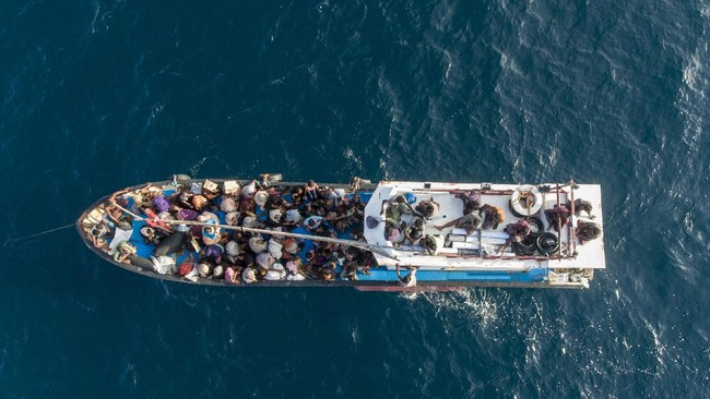 This drone shot shows a boat carrying ethnic-Rohingya Muslims,  off Lhoksukon, North Aceh, Indonesia, Wednesday, June 24, 2020. Indonesian fishermen have discovered over 90 hungry, weak Rohingya Muslims on a wooden boat adrift off Indonesia's northernmost province of Aceh. Police say they were found on the rickety boat about 6 kilometers (4 miles) off the coast. They cried out for help and jumped onto the fishermen's boat, but its engine also stopped working on the way to shore. (AP Photo/Zik Maulana)