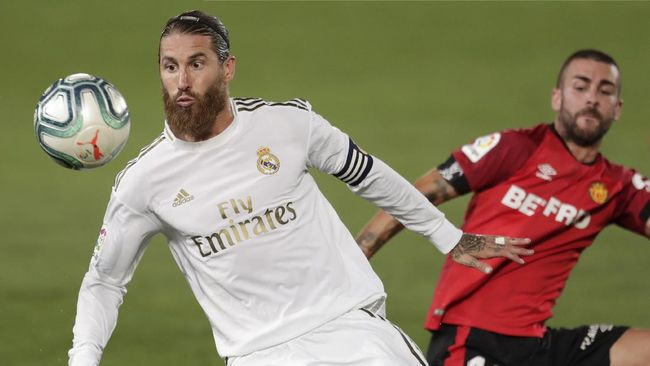 Real Madrid's Sergio Ramos, right, fights for the ball with Mallorca's Dani Rodriguez during the Spanish La Liga soccer match between Real Madrid and Mallorca at Alfredo di Stefano stadium in Madrid, Spain, Wednesday, June 24, 2020. (AP Photo/Bernat Armangue)