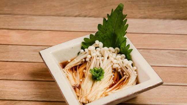 Japanese side dish called Enoki ponzu is boiled enoki mushroom with sweet and sour soy sauce called Ponzu topping with scallion and perilla leaf on brown wooden plate .