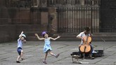 Two children dance as they listen to a street musician on May 22, 2020 in Strasbourg, eastern France, after the city of Strasbourg on May 20, issued a decree making the wearing of masks