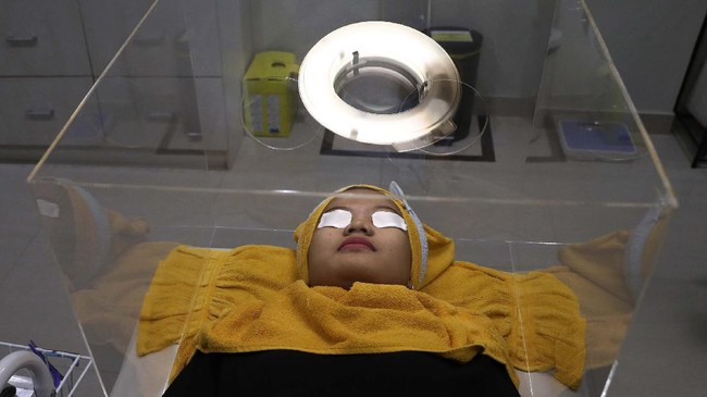 A patient waits for treatment inside a protective acrylic box used as a precaution against the new coronavirus outbreak at the beauty clinic at Tambak Hospital in Jakarta, Indonesia, Tuesday, June 23, 2020. (AP Photo/Tatan Syuflana)