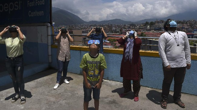 A group of bystanders wear a pair of viewing goggles to watch an annular solar eclipse in Kathmandu on June 21, 2020. (Photo by PRAKASH MATHEMA / AFP)