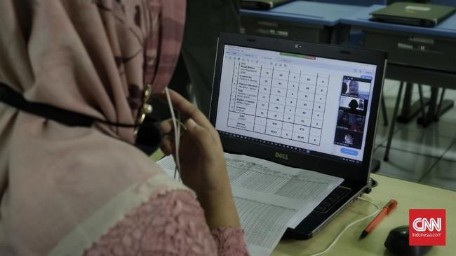 Guru membacakan laporan hasil belajar (Rapor) kenaikan kelas kepada wali murid di SD Yasporbi I Pancoran, Jakarta, Jumat, 26 Juni 2020. CNN Indonesia/Adhi Wicaksono