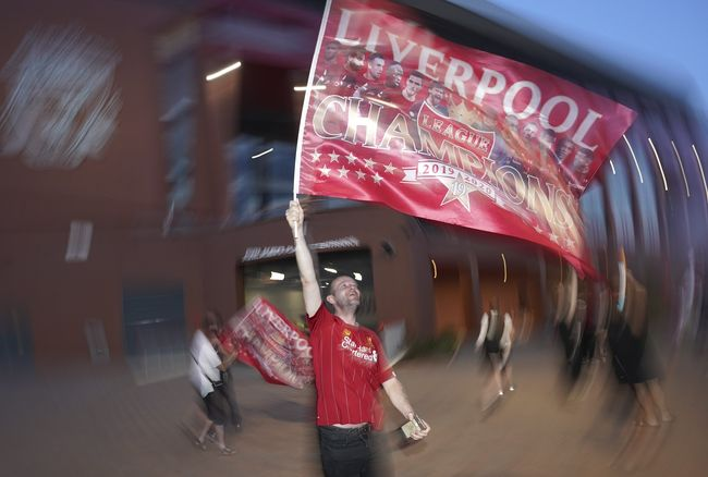 Liverpool supporters celebrate as they gather outside of Anfield Stadium in Liverpool, England, Friday, June 26, 2020 after Liverpool clinched the English Premier League title. Liverpool took the title after Manchester City failed to beat Chelsea on Wednesday evening. (AP photo/Jon Super)