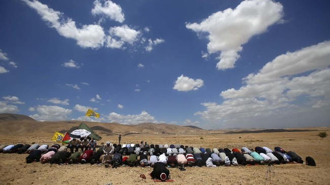 Palestinians pray during a protest against Israel's plan to annex parts of the West Bank and Trump's mideast initiative, in Jordan Valley, Friday, Jun. 19, 2020. (AP Photo/Majdi Mohammed)