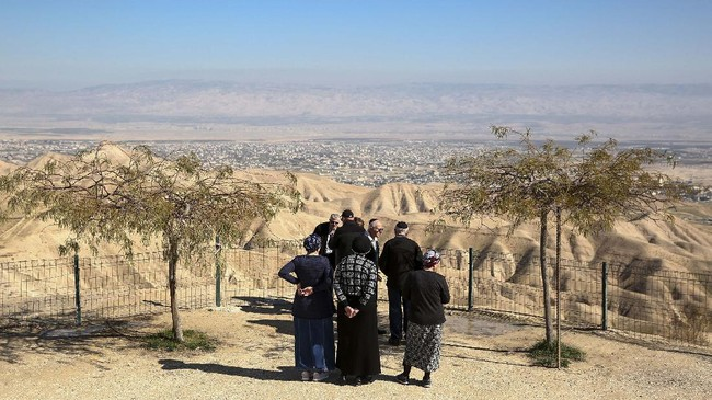 File - In this Sunday, Jan. 26, 2020 file photo, Jewish settlers stand at a view point overlooking the West Bank city of Jericho from the Jewish settlement of Mitzpe Yeriho. Israeli Prime Minister Benjamin Netanyahu has vowed to annex the valley and all of Israel's far-flung West Bank settlements, in line with President Donald Trump's Middle East plan, which overwhelmingly favors Israel and has been rejected by the Palestinians. (AP Photo/Oded Balilty, File)