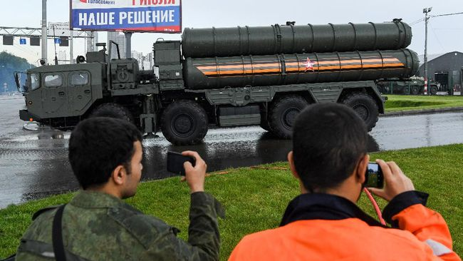 Russian S-400 Triumf surface-to-air missile launchers roll ahead of a second night of rehearsals for the WWII Victory Parade in front of a banner informing of a national vote on constitutional changes in Moscow on June 18, 2020. - Russia's President Putin on June 24 will preside over a massive military parade to mark Soviet victory in World War II, which was postponed due to the coronavirus pandemic. (Photo by Kirill KUDRYAVTSEV / AFP)