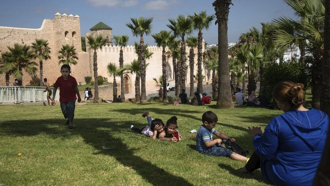 Families spend time at a reopened park after lockdown measures were lifted in Rabat, Morocco, Friday, June 26, 2020. In the capital Rabat, people welcomed the end of lockdown with the joy of a religious holiday. They met friends, planned days at the beach, and visited relatives. (AP Photo/Mosa'ab Elshamy)