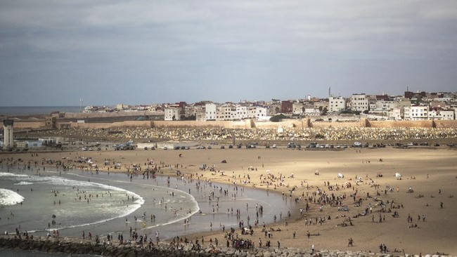 People gather at a reopened beach on the first weekend after lockdown measures were lifted in Sale, Morocco, Friday, June 26, 2020. Moroccans are re-experiencing a taste of the life before. In newly opened public spaces, every sip of coffee in a cafe, every dip in a river with friends, every moment of outdoor intimacy is savored, marking the end of more than three months of lockdown. (AP Photo/Mosa'ab Elshamy)