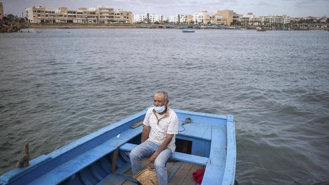 A man crosses by boat from Rabat to Sale after lockdown measures were lifted, in Morocco, Friday, June 26, 2020. Moroccans are re-experiencing a taste of the life before. In newly opened public spaces, every sip of coffee in a cafe, every dip in a river with friends, every moment of outdoor intimacy is savored, marking the end of more than three months of lockdown. (AP Photo/Mosa'ab Elshamy)