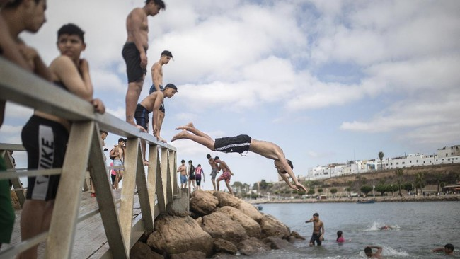 Boys jump into a river to cool down after lockdown measures were lifted in Rabat, Morocco on Friday, June 26, 2020. Moroccans are re-experiencing a taste of the life before. In newly opened public spaces, every sip of coffee in a cafe, every dip in a river with friends, every moment of outdoor intimacy is savored, marking the end of more than three months of lockdown. With the exception of a few cities still struggling with high coronavirus infections, Morocco started entering new normality Thursday as the drum of social life began beating again. (AP Photo/Mosa'ab Elshamy)