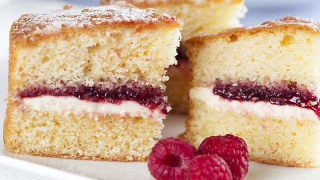 Victoria sponge cake with cream and jam filling, served with raspberries