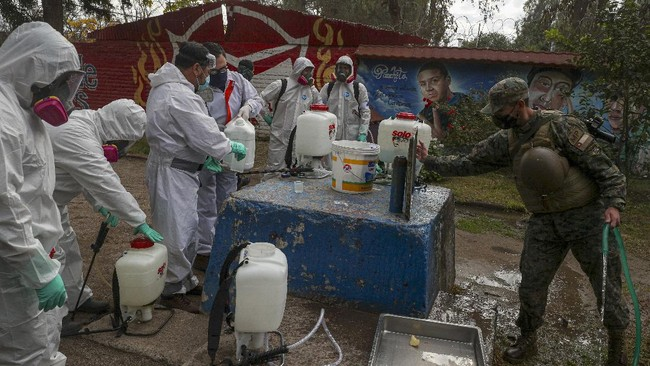 Soldiers in full protection gear prepare to disinfect an area during an event where an army kitchen was serving food for people facing hardship because of lost income due to the new coronavirus pandemic, in Maipu, on the outskirts of Santiago, Chile, Tuesday, June 16, 2020. (AP Photo/Esteban Felix)