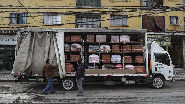 Bergut Funeral Services employees deliver coffins to a funeral store in Santiago, Chile, Friday, June 19, 2020. Coffin production has increased 120%, according to owner Nicolas Bergerie. A basic coffin penned the COVID model was designed to cope with the increase of deaths during the new coronavirus pandemic. (AP Photo/Esteban Felix)