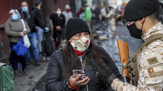 A solider checks the identification of a shopper as she seeks authorization to enter La Vega market, amid the new coronavirus pandemic in Santiago, Chile, Friday, June 26, 2020. (AP Photo/Esteban Felix)