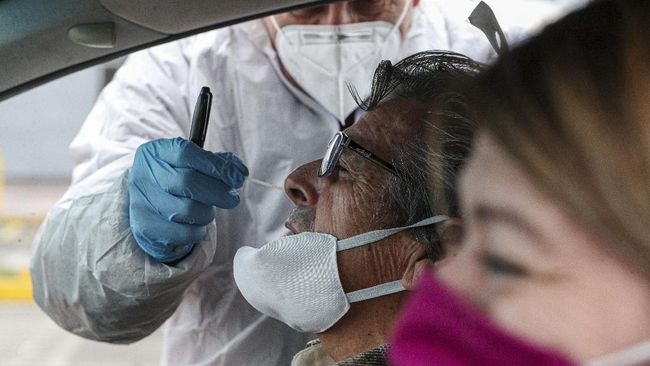 Healthcare worker Patricio Candia takes a nasal swab sample from a man at a new coronavirus testing site, outside a supermarket in Santiago, Chile, Saturday, June 27, 2020.(AP Photo/Esteban Felix)