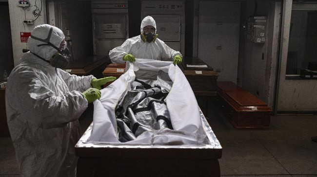 Employees prepare to cremate the body of a person who died from the new coronavirus, at La Recoleta crematorium in Santiago, Chile, Saturday, June 27, 2020. The Ministry of Health reported on Saturday the highest number of deaths in Chile since the start of the pandemic. (AP Photo/Esteban Felix)