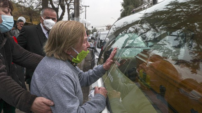 A friend of 72-year-old Monica Lagos, touches the hearse with the coffin containing her body, outside her home in Santiago, Chile, Monday, June 15, 2020. According to grandaughter Ninoska Vasquez, who works as an assistant at a health center, Lagos died from complications related to COVID-19. (AP Photo/Esteban Felix)
