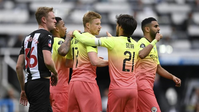 Manchester City's Kevin De Bruyne, center, celebrates after scoring the opening goal from the penalty spot during the FA Cup sixth round soccer match between Newcastle United and Manchester City at St. James' Park in Newcastle, England, Sunday, June 28, 2020. (Shaun Botterill/Pool via AP)