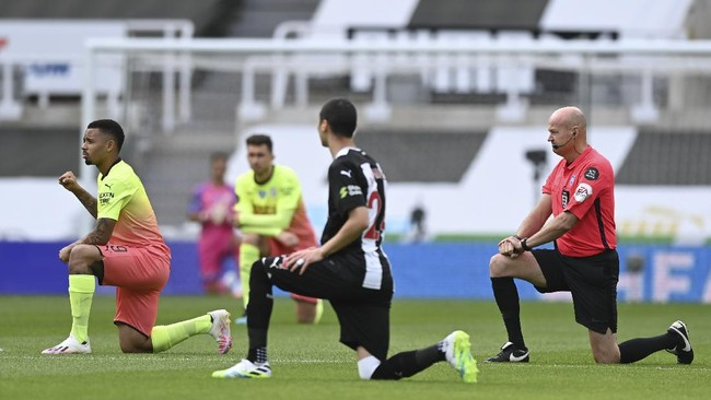 Manchester City's Gabriel Jesus, left, and referee Lee Mason take a knee before the FA Cup sixth round soccer match between Newcastle United and Manchester City at St. James' Park in Newcastle, England, Sunday, June 28, 2020. (Shaun Botterill/Pool via AP)