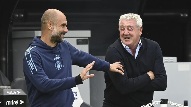 Manchester City's head coach Pep Guardiola, left, shares a joke with Newcastle's head coach Steve Bruce before the FA Cup sixth round soccer match between Newcastle United and Manchester City at St. James' Park in Newcastle, England, Sunday, June 28, 2020. (Shaun Botterill/Pool via AP)