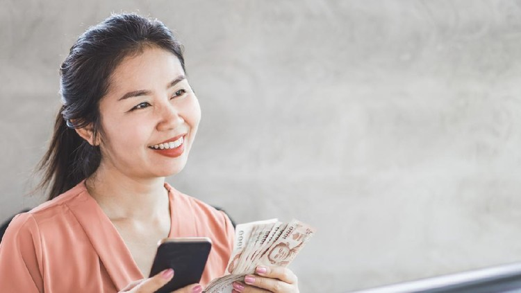 happy Asian woman hand holding smart phone and banknotes ,make money online concept