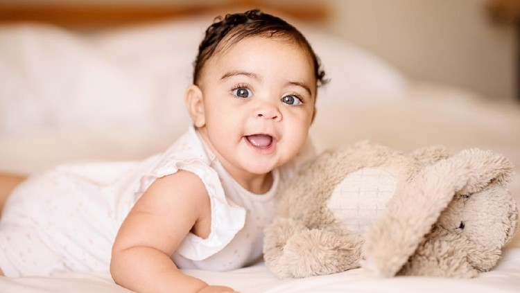 Shot of a cute baby girl on bed with a soft toy